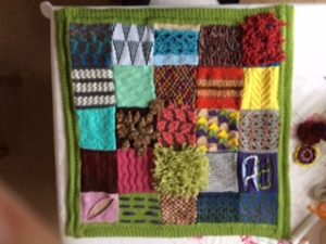 Front of lap blanket with patchwork of many different knitting techniques in seasonal colours